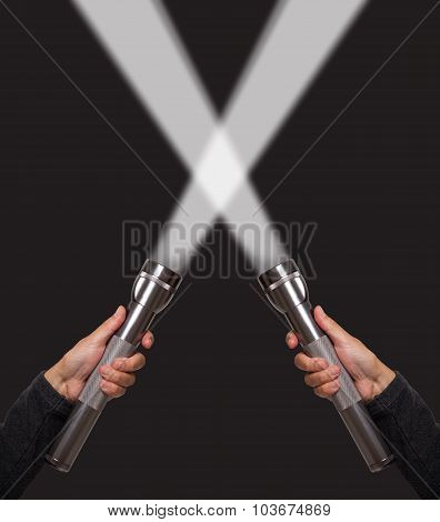 Hands holding flashlights