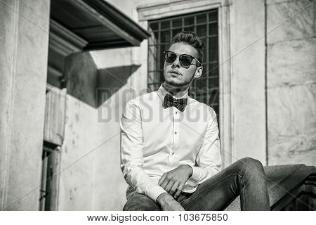 Attractive young man sitting in city wearing sunglasses