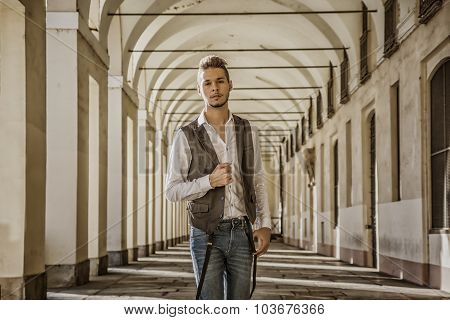 Handsome young man standing outdoors under old colonnade