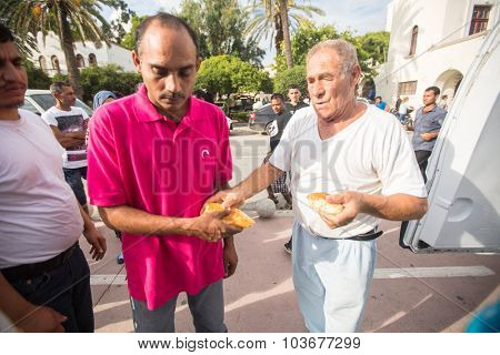 KOS, GREECE - SEP 28, 2015: War refugees receive humanitarian assistance - bread. More than half are migrants from Syria, but there are refugees from other countries-Afghanistan, Pakistan, Iraq, Iran.