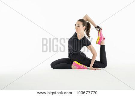 Rhythmic gymnast doing exercise in studio.