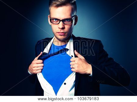 Businessman pulling open his shirt like a superhero