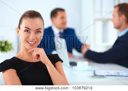 Portrait of a beautiful businesswoman sitting in an office with colleagues shaking hands in the back