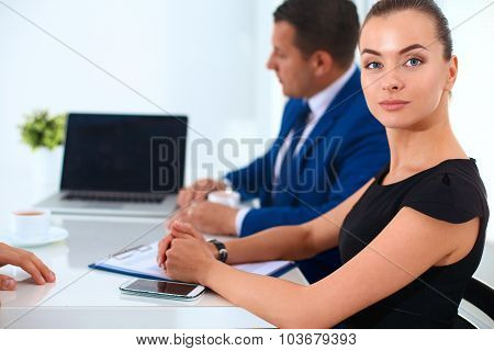 Portrait of a beautiful businesswoman sitting in an office with colleagues in the background