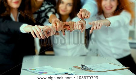 A group of positive colleagues pointing their fingers at the camera
