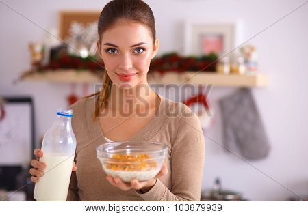 A young woman eating cereals in her kitchen