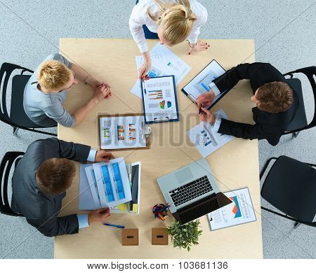 Top view of office workers sitting at a table for meetin