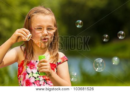 Little Girl Child Blowing Soap Bubbles Outdoor.