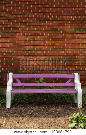 Purple bench on a brick wall