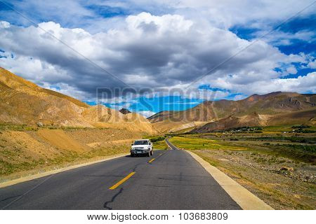 A car in the road among beautiful landscape in Tibet, China.