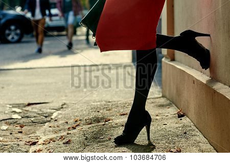 Sexy woman wearing black high heel shoes in city