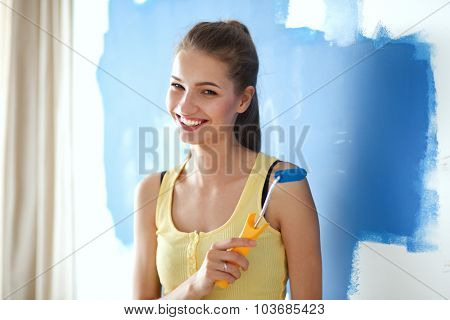 Beautiful young woman doing wall painting standing .
