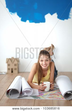 Young woman lying on the floor and looking at blueprint of new house