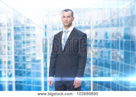 Portrait of serious businessman, blue background