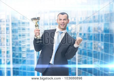Portrait of fists gesturing businessman with gold cup, blue background