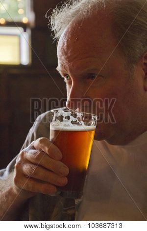 Middle Aged Man Drinking An Amber Glass Of Beer