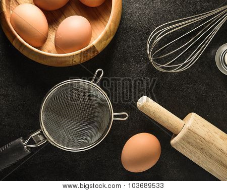 Kitchen utensils and baking ingredients: egg and flour on black background copy-space.