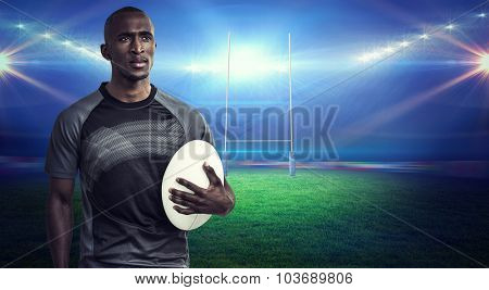 Thoughtful athlete holding rugby ball against rugby stadium