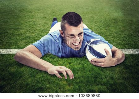 Confident rugby player lying in front with ball against green field