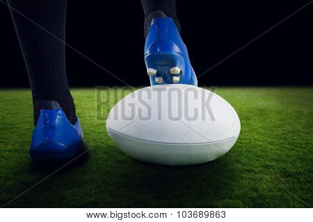 Rugby player posing feet on the ball against green field