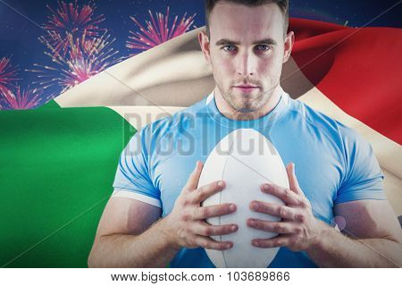 Rugby player looking at camera with ball against fireworks exploding over football stadium