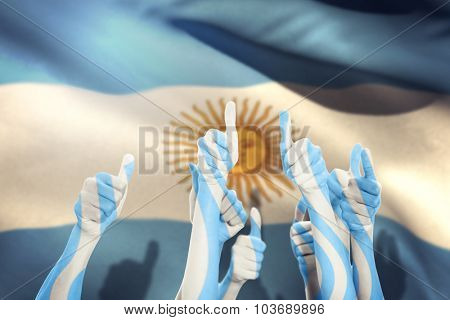 Hands up and thumbs raised against argentina flag against white background