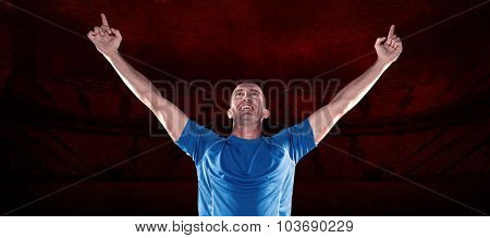 Happy rugby player with arms raised against rugby stadium