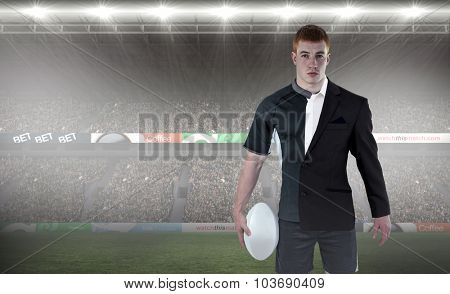 Rugby player holding a rugby ball against rugby fans in arena
