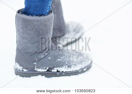 people, footwear, winter and clothing concept - close up of woman legs wearing warm boots on snow