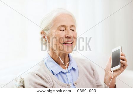 technology, age and people concept - happy senior woman with smartphone and earphones listening to music at home
