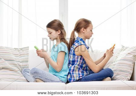 people, children, technology, friends and addiction concept - little girls with smartphones sitting on sofa back to back at home
