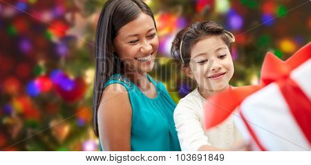 holidays, birthday, family, childhood and people concept - happy mother and little girl with gift box over lights background
