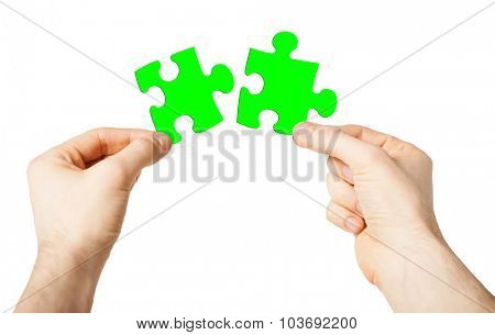 nature, ecology, energy saving and people concept - close up of male hands trying to connect green puzzle pieces
