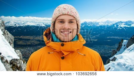 winter, leisure, clothing and people concept - happy teenage boy or young man in winter clothes outdoors over snowy mountains background