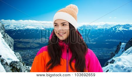 winter, leisure, clothing and people concept - happy young woman or teenage girl in winter clothes outdoors over snowy mountains background
