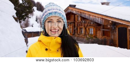 winter, leisure, clothing and people concept - happy young woman in winter clothes outdoors over wooden country house background and snow