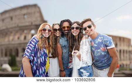 summer vacation, travel, tourism, technology and people concept - smiling young hippie friends taking picture by smartphone selfie stick over coliseum in rome background