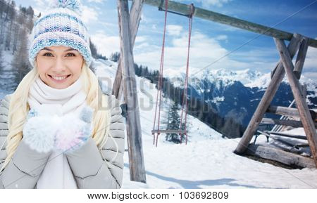 season, christmas and people concept - happy smiling young woman holding snow on palms over winter landscape