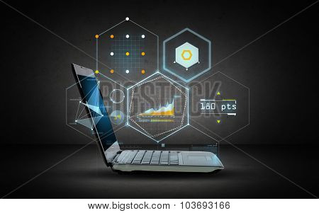 technology and future concept - open laptop computer with virtual chart projection over dark gray background
