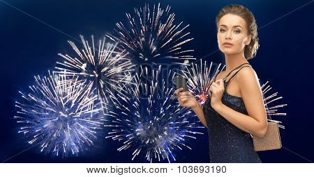 people, luxury, night life and finance concept - beautiful woman in evening dress with vip card and bag over firework on dark blue background