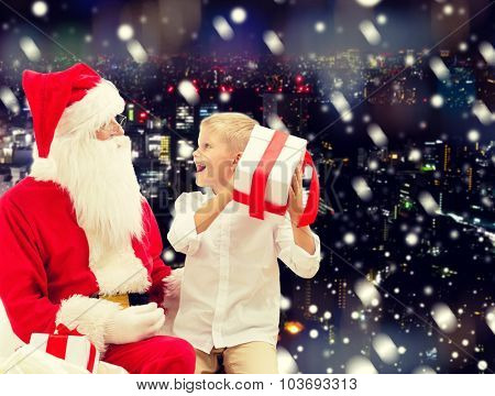 holidays, christmas, childhood and people concept - smiling little boy with santa claus and gifts over snowy city background