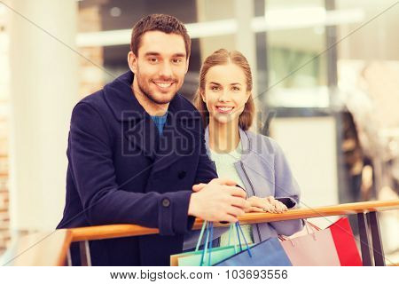 sale, consumerism and people concept - happy young couple with shopping bags in mall