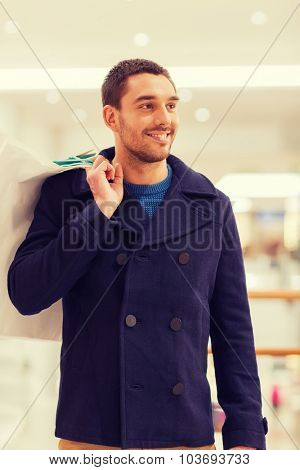 sale, consumerism and people concept - happy young man with shopping bags in mall