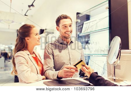 sale, consumerism, shopping and people concept - happy couple with credit card at jewelry store in mall