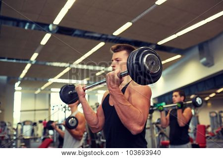 sport, bodybuilding, lifestyle and people concept - young men with barbells flexing muscles in gym