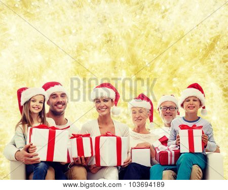 family, happiness, generation, holidays and people concept - happy family in santa helper hats with gift boxes sitting on couch over yellow lights background