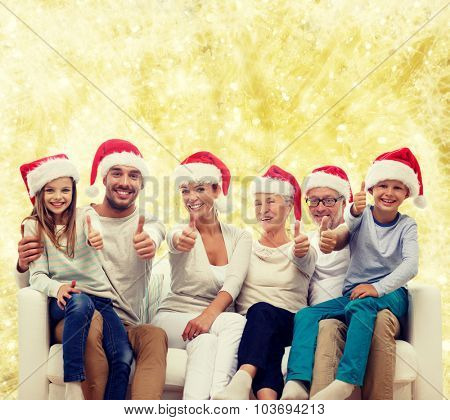 family, happiness, generation, holidays and people concept - happy family in santa helper hats sitting on couch and showing thumbs up gesture over yellow lights background