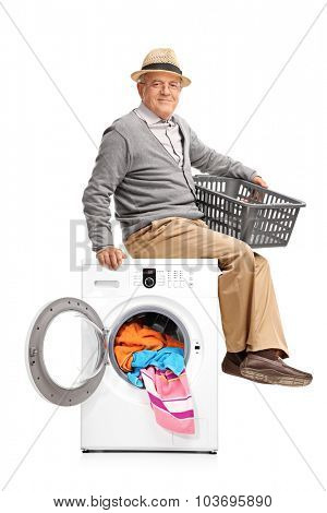 Vertical shot of a senior gentleman sitting on a washing machine and waiting for the laundry isolated on white background
