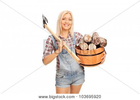 Young blond woman in checkered shirt holding a bucket full of logs and carrying an axe over her shoulder isolated on white background