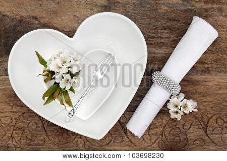 Romantic table place setting with white heart shaped porcelain bowls, antique silver fork with flower blossom and napkin with ring over old oak background.